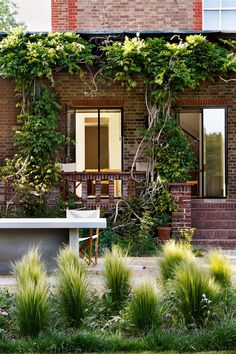 """Grasses are planted in front of the original wisteria-hung loggia at [link url=""""http://www.houseandgarden.co.uk/gallery/modern-minimalism-in-an-edwardian-villa""""]this house designed by William Smalley[/link], while a stone table on the patio makes a great permanent dining space."""