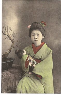 Young maiko holding a doll. 1910. One of the ubiquitous photographs of Maiko (geisha/prostitutes in training) with dolls. It was apparently sexy for them to look even more childlike than they really were.