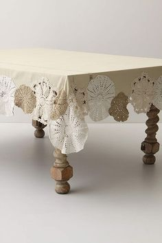 Beautiful doilies reborn as embellishment for an otherwise plain table cloth. You could do this with a red table cloth as well with white doilies for a more festive Christmas approach.