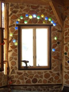Coloured bottles around cordwood house window