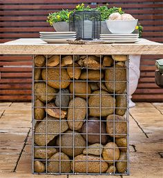 Use gabion baskets - or make your own using steel mesh - fill with pebbles or stone and add reclaimed wood or railway sleeper tops and you have a modern outdoor dining set that is easy to make, won't cost a fortune and is practically maintenance free! Outdoor Table Settings, Outdoor Dining, Outdoor Tables, Concrete Outdoor Table, Outdoor Seating, Fire Pit Furniture, Garden Furniture, Outdoor Projects, Garden Projects