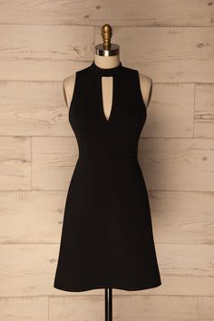 Urzelina #boutique1861 / Here's the ultimate little black dress for all your glamorous and festive outings! Its modern style is undeniable thanks to the V cut out in the front and back and choker-style neck. Add a pair of timeless pumps and you're ready to start turning heads!