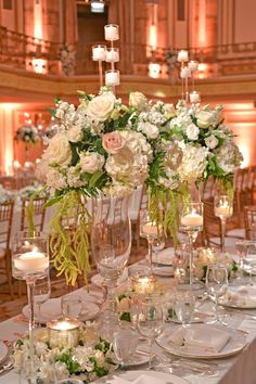 Fluted glass vessels were topped with textured arrangements of ivory hydrangea blossoms and roses. The towering arrangements were interspersed with candles in mercury-glass hurricanes surrounded by wreaths of white and green florals. #centerpiece #candles Photography: Carasco Photography. Read More: http://www.insideweddings.com/weddings/bride-wears-custom-ines-di-santo-gown-at-glamorous-chicago-wedding/550/