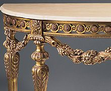 Louis XVI style carved wood console table with floral garland motif, antique gold-leaf finish and Estremoz marble top with curved beveled edge