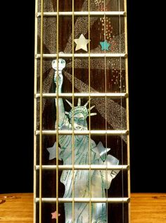 """Custom-made acoustic dreadnought guitar with """"Patriot"""" motif hand-carved artistic decorations on the body, neck and headstock. Guitar Inlay, Guitar Neck, Wine Rack, Ladder Decor, Blueberry, Hand Carved, Acoustic Guitars, Exotic, Universe"""