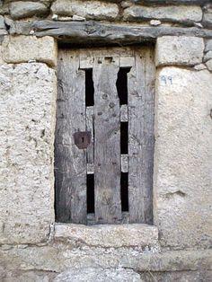 La puerta corresponde a una de las bodegas del Barrio de Bodegas de Baltanás. Sillería de piedra, escalón de aceso y dintel de viga de enebro. La puerta es de gruesa madera y en ella pueden apreciarse una serie de aperturas para ventilación de la bodega formando un enrejado con la propia escuadría de los elementos que la conforman. Palencia. Arlanza.