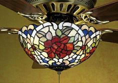 27458 Features: -Fan light fixture.-Single cabernet red rose.-Framed in sunset green leaves and ivory scrolls sits on lavender and plum bronze lace.-Beautiful Tiffany style stained glass fan light sh...