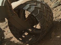 The left-front wheel of NASA's Curiosity Mars rover shows dents and holes in this image taken during the 469th Martian day, or sol, of the rover's work on Mars (Nov. 30, 2013).