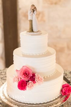 So in love with this simple, white wedding cake!  Small bunches of pink blooms decorate the cake with a darling Willow Tree husband and wife cake topper.  The perfect wedding cake for your pink wedding:  round, three-tiered, and white. Photo taken at THE SPRINGS Event Venue.  Follow this pin to our website for more information, or to book your free tour! SPRINGS location:  Stonecreek Hall in Katy, TX Photographer:  C Baron Photography #weddingcake #weddingcakeideas #pinkwedding #willowtree