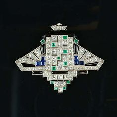 Art deco gem-set and diamond lapel watch, circa the pierced geometric plaque with sloping shoulders and crenellated termination, pierced and millegrain-set with old brilliant and single-cut diamonds and highlighted by square-cut emeralds and sapphir Bijoux Art Deco, Art Deco Jewelry, Fine Jewelry, Jewellery, Art Nouveau, Belle Epoque, Mode Rococo, Antique Jewelry, Vintage Jewelry