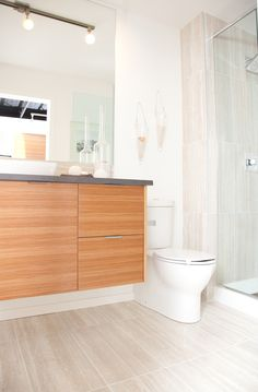 Glass shower door and echo wood floating cabinets in modern bathroom at The Block by Avi Urban