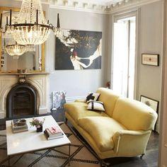 Jenna Lyons living room // lemon yellow George Smith English roll arm sofa, French crystal chandelier, Moroccan rug, light gray walls, Brooklyn brownstone
