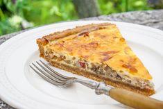Slaný koláč z křehkého špaldového těsta s náplní z cibule, libové slaniny, zakysané smetany, vajec a čedaru, okořeněný provensálskými bylinkami.