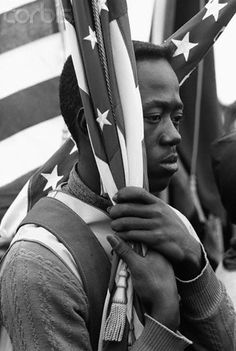 A young man holds the American flag during the Selma to Montgomery Civil Rights March, 1965.