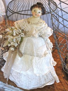 Every doll is unique and hand-sculpted of papier mache on a cloth body and costumed in antique fabrics.