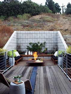 A concrete block retaining wall is a good solution for building a modern deck into a hillside. I love the Corten steel fire pit, and how they painted just . Sloped Yard, Sloped Backyard, Backyard Landscaping, Terraced Landscaping, Backyard Ideas, Steep Backyard, Backyard Movie, Backyard Seating, Backyard Patio