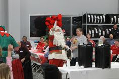 Santa greets employees of Wilson Toyota of Ames and their families during the dealership's annual Christmas Party for children from Lutheran Services in Iowa's Beloit Residential Center Tuesday night. Photo by Michael Crumb/Ames Tribune http://www.amestrib.com/news/20161213/meaning-of-christmas