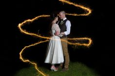 The bride & groom surrounded by a sparkler trail on their wedding day at Jimmy's farm. Suffolk. www.headoverheelsphotography.co.uk