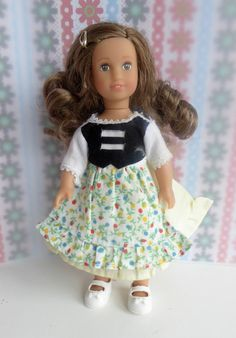 Sweet little vintage dress with attached flowery apron and black bodice over pale yellow and white dress, fastening with velcro at the back.