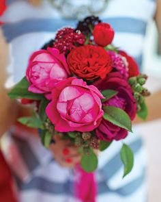bouquet of red and fuchsia cabbage roses and scabiosa, lush island foliage, and raspberries on the vine.