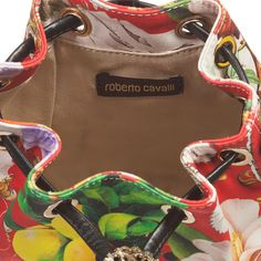 Girls gorgeous bucket style shoulder bag by Roberto Cavalli. Made from cotton fabric, it features the designer's pink 'wonderland' floral, fruit and butterfly print. It has one compartment with a cotton lining, large enough to carry small essential items, such as a mobile phone. It has a synthetic adjustable shoulder strap and drawstring fastening with a gold metallic 'RC' logo and tassels.
