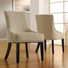 side chairs with curved arm detail and nailheads; Velvet fabric  Upholstery color: Sandstone beige  Nailhead trim  Flared legs  Seat height: 18 inches  Dimensions: 36 inches high x 24 inches wide x 22 inches deep; $270 for 2