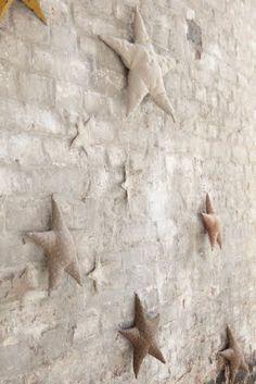 Natural linen fabric stars, strewn over a like-hued painted brick wall. Christmas Love, Christmas Crafts, Christmas Decorations, Xmas, Christmas Ideas, Christmas Ornaments, Deco Nature, Fabric Stars, Star Wall
