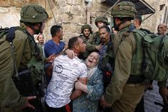 A woman tries to prevent the arrest of a Palestinian man by Israeli soldiers in West Bank, Palestine. (HAZEM BADER / AFP - Getty Images)