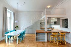 Svou roli hraje v interiéru i geometrický vzor na čelní obývací stěně a židle ve výrazné tyrkysové barvě. Vyšší stropy umožnily vznik patra.