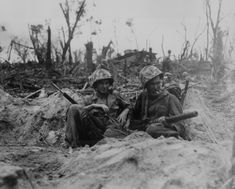 Marine Pfc. Douglas Lightheart (right) cradles his 30-cal. machine gun in his lap, while he and his buddy Pfc. Gerald Churchby take time out for a cigarette, while mopping up the enemy on Peleliu Is. Photograph by Cpl. H. H. Clements, taken on September 14, 1944.