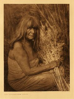"""Hipah with arrow-brush - Maricopa, 1907. Curtis Caption: """"Arrow-brush is extensively used by the tribes of this region as a covering for their houses. In earlier time they lived in circular houses constructed of a framework of heavy poles covered with arrow-brush and coated with mud. In many of the modern rectangular houses, also, the arrow-brush is used, bound together closely with withes, and plastered on the outside with adobe."""""""