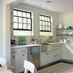 kitchens - white cabinets stainless steel apron sink white carrara marble countertops black floating shelves white green gray striped rug subway tiles backsplash