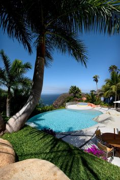 Palm trees create a tropical frame for this luxurious pool deck overlooking the ocean in Puerto Vallarta. A blue outdoor sofa and shaded lounging areas provide ample space to enjoy this dreamy environment.