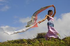 Beautiful woman playing in the wind on top of a bluff in Maui