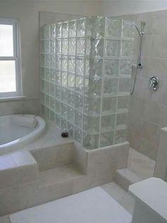Ladrillos de vidrio dividiendo bañera de ducha.