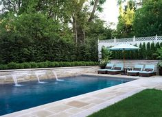 A simple backyard pool is elevated by the addition of waterfalls.