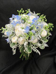 Brides bouquet of white ranunculus, blue delphinium and dusty miller