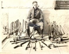 A police officer poses with opium pipes, opium lamps, and other paraphernalia confiscated at opium den raids in San Francisco