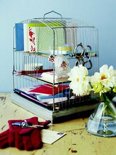 How clever! Mail Cage - This old birdcage is the perfect place to stash mail and letter-writing essentials. To create your own cagey storage solution, scrub the framework of the cage with a bleach solution. Then clip off the wire from the front and back, leaving a few rows to act as mail slots. To create shelves, cut dowel rods slightly longer then the cage width and notch the wood to help it grab the wire. Cut glass or plexiglass shelves to fit and rest them on the dowel rods.