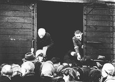 Jews being deported from the Warsaw ghetto board a freight train. Warsaw, Poland, July-September 1942.