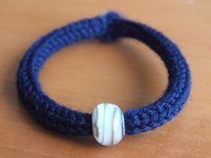 Bracciale blu con pietra e chiusura con bottoncino.
