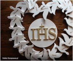 Styropianowe gołębie z imionami dzieci najlepiej wpasowują się w komunijne aranżacje. Jest to dekoracja, która nawiązuje swoim kształtem do charakteru tego święta. Do tej kompozycji użyto również styropianowej hostii ze złotymi literami IHS.