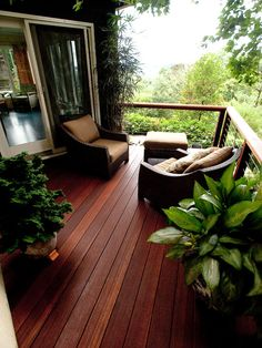 the rich wood decking and dark wicker furniture compliment the lushness of the landscape
