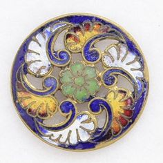"Primarily in blue, this antique champleve enamel button also has red, white, orange and green enamel that is accented by pierced open work. The button measures 1 1/16"" in diameter."
