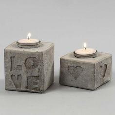 Kirjaimilla ja kuvioilla koristellut kynttilänjalat