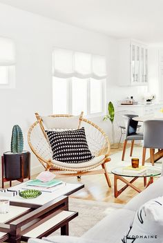 A fashion blogger's living room with a neutral color palette, and a a seating area with a wooden circle armchair
