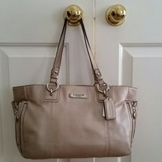 Coach Gallery Tote + Bonus Wallet This chic, luxurious, Gallery tote is BEAUTIFUL! The champagne colored exterior features incredibly soft leather, zip side pockets, a long slip pocket on back, and silver tone hardware. The pink, satin interior features a zip pocket and 2 multifunction pockets. The pink, leather, accordian style, zip around wallet features a front slip pocket on exterior, 2 long multifunction pockets, divider, and plenty of card slots on interior. The bag is like new! The…