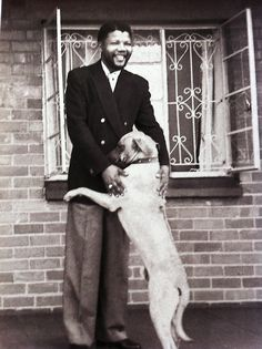 A young Nelson Mandela, receiving a hug from a dog. This is awesome.
