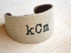 typeset monogrammed linen covered customizable cuff. $24.95, via Etsy.