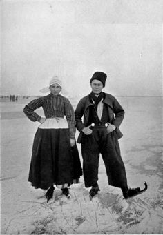 """Photo. byWeenenk & Snel.  YOUNG VOLENDAMMERS SKATING.  The lad is calling attention to his valuable silver """"breech-pieces."""" The girl is wearing the Volendam cap with its stiffly starched cornettes."""